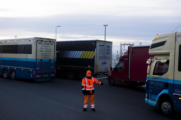 A worker directs trucks where to wait in line in order to board ferries to the United Kingdom in Calais, France. Twenty percent of British imports pass through the port of Calais.