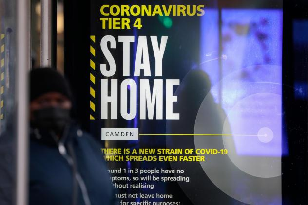 A poster about the new, fast-spreading variant of the coronavirus warns some Britons to stay home. The sign is displayed near King's Cross railway station in London.