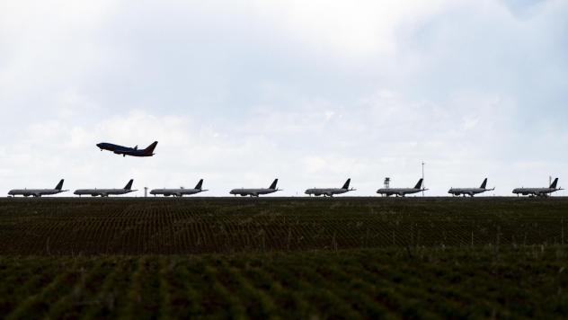 A Southwest Airlines flight takes off as United Airlines planes sit parked on a runway at Denver International Airport in April.