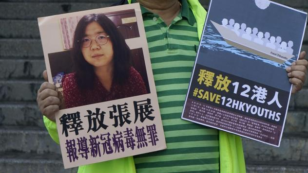 A pro-democracy activist holds placards with the picture of Chinese citizen journalist Zhang Zhan outside the Chinese central government's liaison office, in Hong Kong, Monday. Activists demand the release of Zhang, as well as the 12 Hong Kong activists