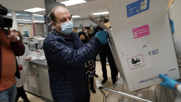 Colorado Gov. Jared Polis helps put the state's first shipment of COVID-19 vaccine in a freezer last week at a state health department laboratory.