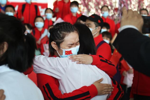 Health workers from Tongji Hospital in Wuhan, China, share an emotional embrace with their peers from a hospital in Jilin province at the Tianhe Airport. Colleagues who worked on the front lines together bid farewell as Wuhan lifted its coronavirus lockd