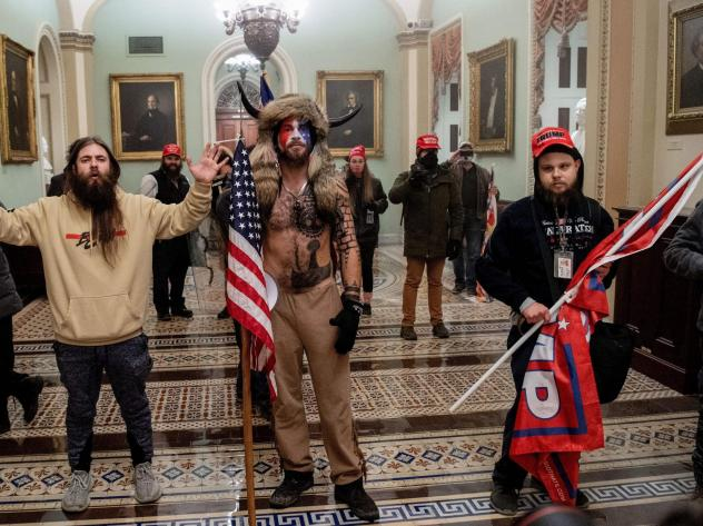 Supporters of President Trump, including Jake Angeli (center), a QAnon supporter known for his painted face and horned hat, stand inside the U.S. Capitol on Jan. 6. Demonstrators breached security and entered the Capitol as Congress was in the process of