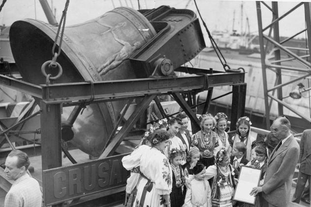 A group of former displaced persons helps load the Freedom Bell aboard a Navy transport vessel in Brooklyn, N.Y., on Oct. 9, 1950. One of the children, Eva Zandler, 8, originally from Poland, presents a scroll — to be enshrined in the Freedom Bell's to
