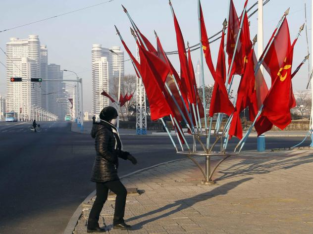 A person passes by a bouquet of Workers Party flags along a main street of the Central District in Pyongyang, North Korea, last week.