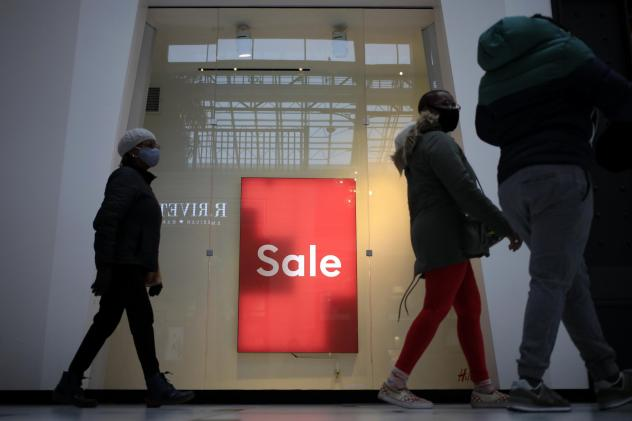 """Shoppers walk past a """"Sale"""" sign outside a store at the Easton Town Center Mall in Columbus, Ohio, on Jan. 7."""