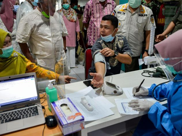 An official has a blood pressure test before receiving the Sinovac coronavirus vaccine, developed in China, at a hospital in Banda Aceh, Indonesia, on January 15.