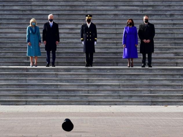 High winds blow a hat by as President Biden, first lady Jill Biden, Vice President Harris and second gentleman Douglas Emhoff walk down the steps of the Capitol.