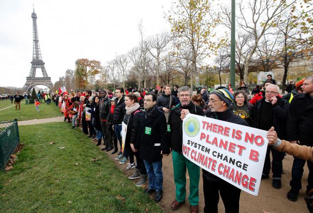 President Joe Biden is directing the U.S. to rejoin the international Paris Climate Agreement, which aims to cut global greenhouse gas emissions. Here, activists rally on Dec. 12, 2015.