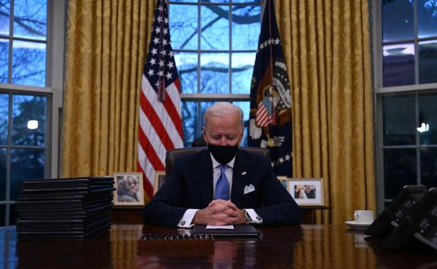President Biden sits in the Oval Office at the White House after being sworn in as the 46th president of the United States on Wednesday.