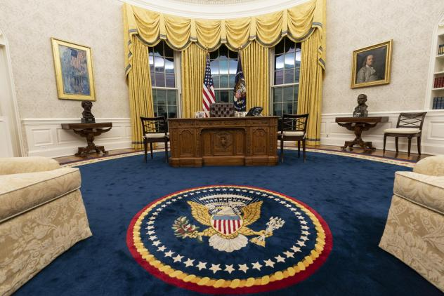 President Biden kept the drapes and most of the furniture, but the rug and artwork in the Oval Office have changed. Flanking the Resolute desk are busts of  Abraham Lincoln, left, and Harry Truman. Above Lincoln is <em>The Avenue in the Rain</em> by Chil