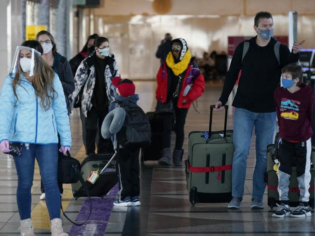Masked travelers head through the main terminal of Denver International Airport on Dec. 31. Starting Feb. 1, travelers will be required to wear face masks on nearly all forms of public transportation.