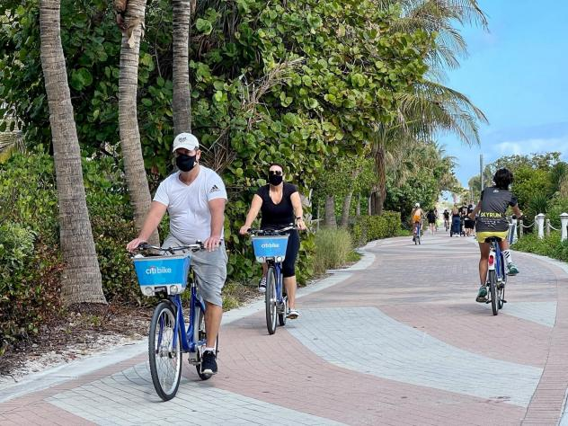 """People bike along the beach in Miami on Dec. 20, 2020. """"People are tired of being at home,"""" one travel advisor says as an industry decimated by the pandemic begins to see small signs that a recovery might be on the way."""