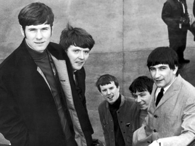 """The Animals, from left, Hilton Valentine, Chas Chandler, John Steel, Eric Burdon and Dave Rowberry, board an airliner in London bound for New York on May 27, 1965, to appear on """"The Ed Sullivan Show"""". Valentine died Friday at the age of 77."""