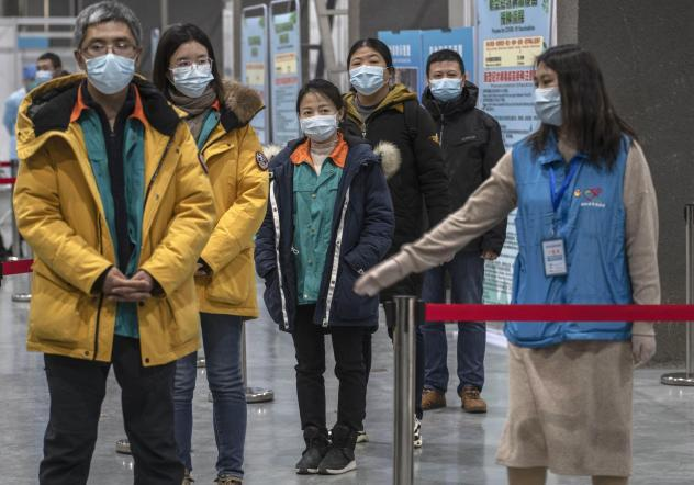 Chinese workers wait to receive a COVID-19 vaccine jab at a mass vaccination center in Beijing on Jan. 5. Even with at least 5 homegrown vaccines nearing approval, China is setting a modest initial goal: 50 million people vaccinated by mid-February — a