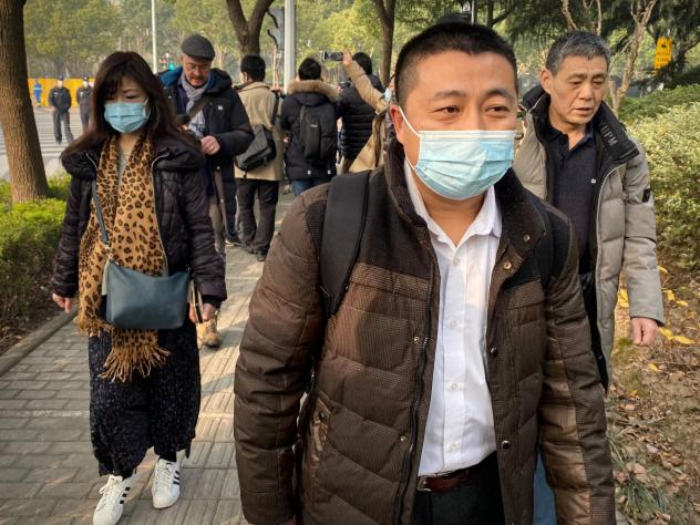 Lawyer Ren Quanniu (center), representing Chinese citizen journalist Zhang Zhan who reported on Wuhan's COVID-19 outbreak and was placed in detention since May, arrives at the Shanghai Pudong New District People's Court where Zhang is set for trial in Sh