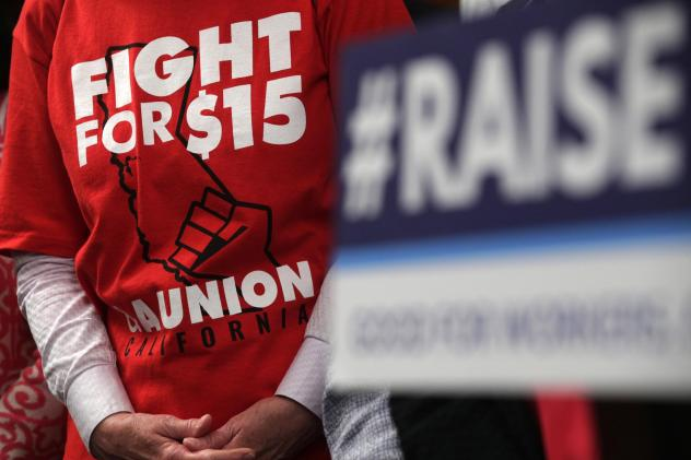 """An activist wears a """"Fight For $15 and a Union"""" t-shirt at the U.S. Capitol in 2019 as lawmakers took on legislation to raise the federal minimum wage."""