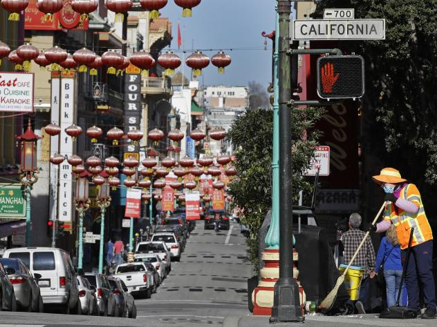 In this Jan. 31, 2020, file photo, a masked worker cleans a street in the Chinatown district in San Francisco. Police and volunteers have increased their street presence after a series of violent attacks against older Asian residents in Bay Area cities s