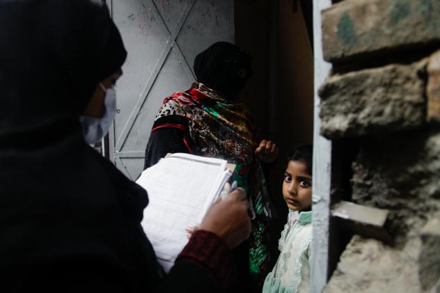 Polio vaccinator Zeenat Parveen, holding the clipboard, and a volunteer go door-to-door to reach children in Rawalpindi, a city near the Pakistani capital of Islamabad.