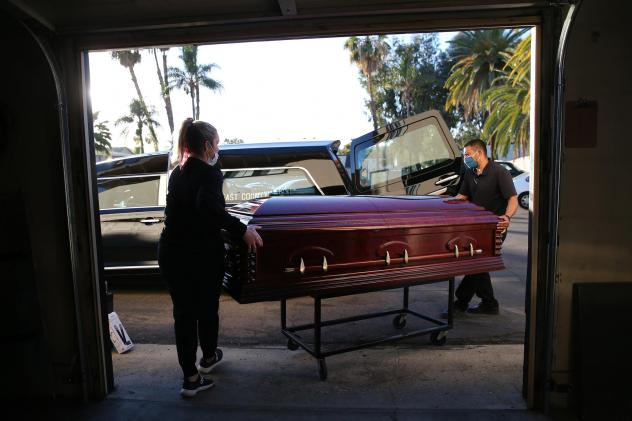 Embalmer and funeral director Kristy Oliver (left) and funeral attendant Sam Deras load the casket of a person who died after contracting COVID-19 into a hearse in El Cajon, Calif. People who work in hospitals and in funeral homes are witnesses to the lo