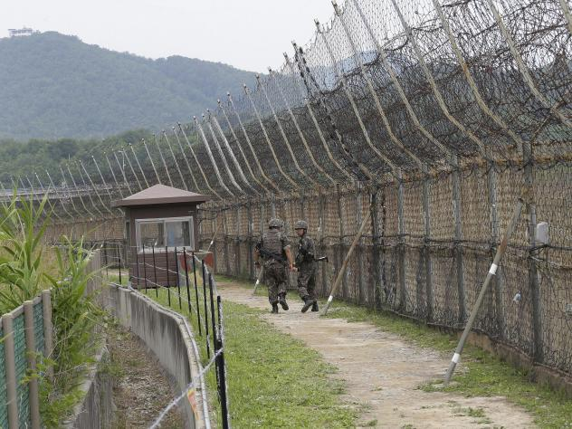 South Korean soldiers patrol while hikers visit the DMZ Peace Trail in the Demilitarized Zone in Goseong, South Korea. A defector from North Korea was apprehended in Goseong last week after evading South Korean guards for hours.