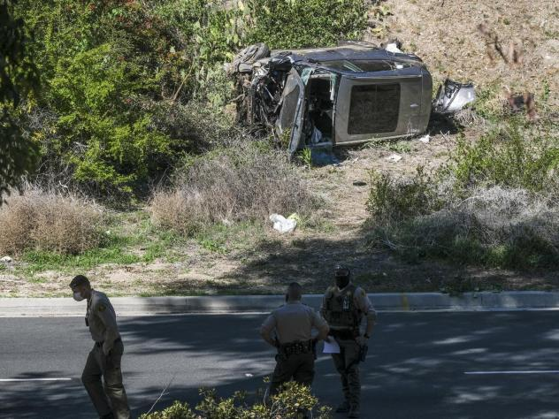 A vehicle rests on its side after a rollover accident involving golfer Tiger Woods along a road in the Rancho Palos Verdes section of Los Angeles County on Tuesday. Woods suffered leg injuries in the one-car accident and was undergoing surgery, authoriti
