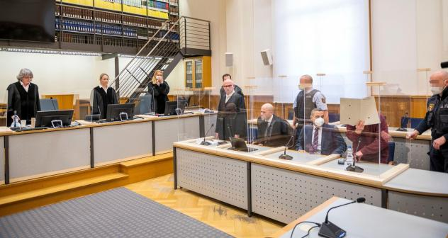 Presiding judge Anne Kerber (left) stands before handing the verdict to Syrian defendant Eyad al-Gharib (right, face hidden under a folder) Wednesday in Koblenz. Gharib, 44, a former Syrian intelligence service agent, was sentenced to 4 1/2 years in jail