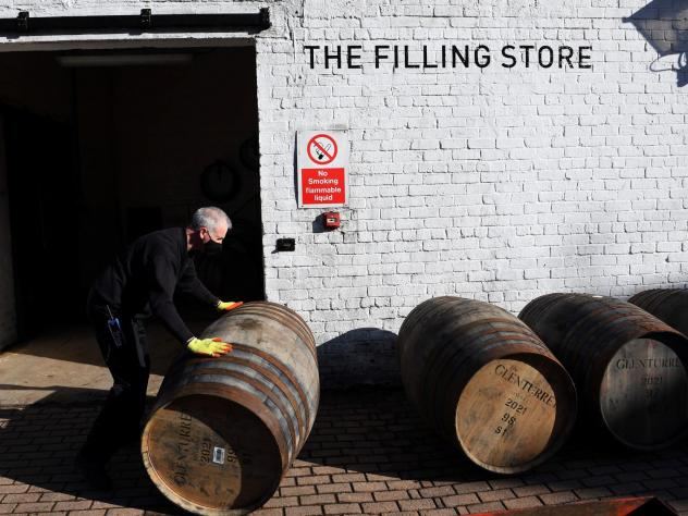 Scotch whisky producers are welcoming news of a breakthrough on tariffs, which came as the industry adjusted to both Brexit and then the COVID-19 pandemic. Here, an employee rolls a whisky barrel at the Glenturret Distillery in Crieff, central Scotland,