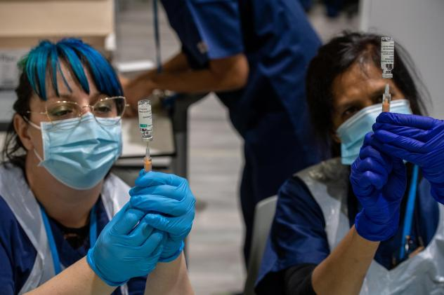 Two health care workers prepare syringes with AstraZeneca's COVID-19 vaccine in London Monday. A U.K. study will expose volunteers to the coronavirus and could help development of future vaccines.