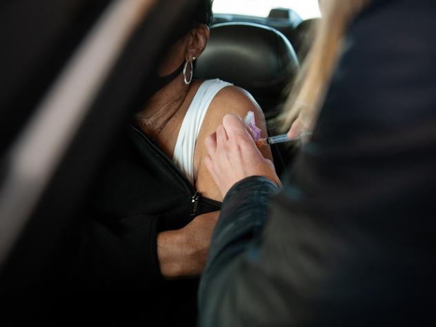 A health care worker at a drive-through site in Greenville, Miss., administers a COVID-19 vaccine shot in January. Mississippi was one of the first states to add a body mass index of 30 or more (a rough gauge of obesity) to its current list of qualifying
