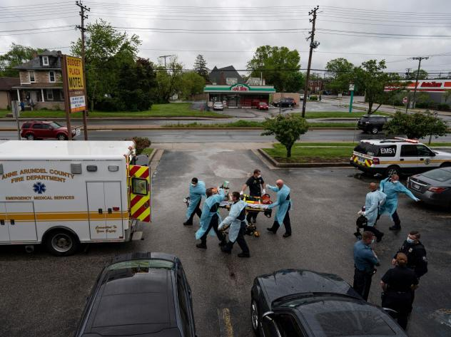 Firefighters and paramedics with the Anne Arundel County Fire Department in Maryland wear enhanced PPE, during the coronavirus pandemic, as they transport a patient after responding to a call for a cardiac arrest as a result of a drug overdose on May 6,
