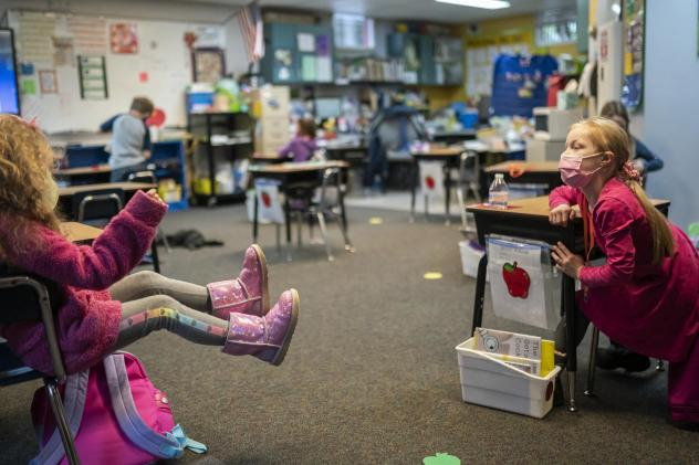 """Two first grade students talk in the back of class at the Green Mountain School last month in Woodland, Wash. The CDC's current guidance for schools recommends seating or desks be """"at least 6 feet apart when feasible."""""""