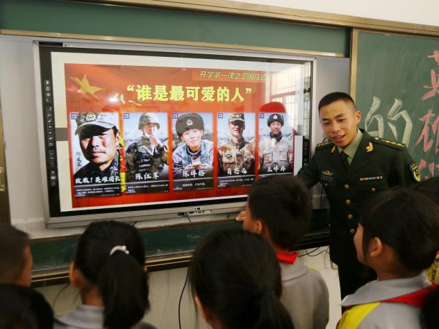A paramilitary police officer talks next to a screen showing frontier soldiers of the People's Liberation Army during an event at a primary school in Wuzhishan, Hainan province, China, on Feb. 22. On the screen are (L-R) Qi Fabao, who was seriously wound