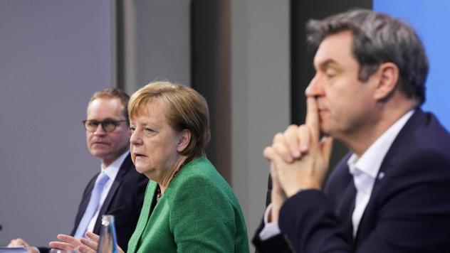 German Chancellor Angela Merkel, with Bavaria's State Premier Markus Soeder (right) and Berlin's Mayor Michael Mueller, participate in a news conference following talks via videoconference with Germany's state premiers on the extension of the current COV