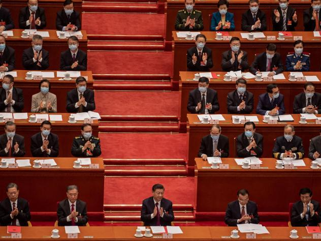 China's President Xi Jinping (C) applauds with other leaders and delegates after they voted on changes to Hong Kong's election system during the closing session of the National People's Congress at the Great Hall of the People in Beijing on March 11, 202
