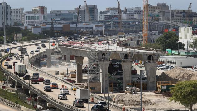 Workers improve a busy highway intersection in Miami. President Biden is proposing roughly $2 trillion to invest in the nation's infrastructure. His plan includes improvements for roads, bridges, transit, water systems, electric grids and Internet access