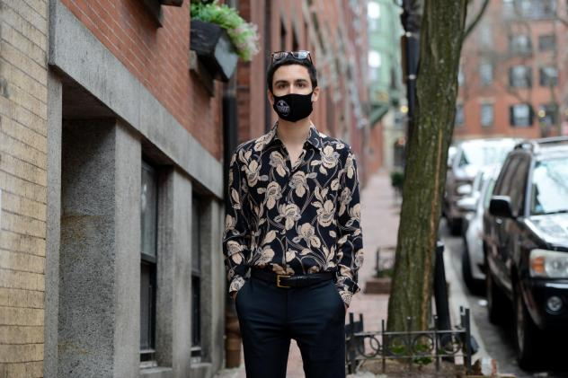 Gabriel Toro, 23, stands on the sidewalk near his apartment in Boston on March 11. Toro completed the credits required for a bachelor's degree from the University of Massachusetts Boston but the school wouldn't release Toro's transcript or degree because