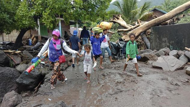 People walk amid debris Sunday in a village affected by flooding in Ile Ape on Lembata Island in Indonesia's East Nusa Tenggara province.