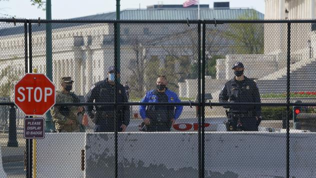 U.S. Capitol Police officers and members of the National Guard keep watch at the Constitution Avenue entrance to the East Plaza of the Capitol where an officer was killed when a man rammed a car into the barricade on April 2. The debate about whether the