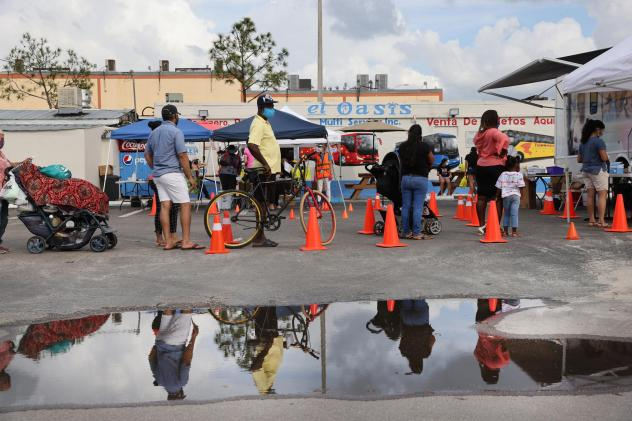 People line up to receive a rapid COVID-19 test on Feb. 17, 2021 in Immokalee, Fla. Immokalee, which has a poverty rate of around 40% and whose population is made up primarily of agricultural workers, has joined with the Coalition of Immokalee Workers an
