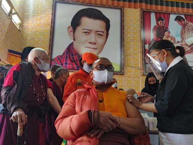 A health worker vaccinates a Buddhist monk sitting in front of a portrait of Bhutanese King Jigme Khesar Namgyel Wangchuck at a secondary school in Bhutan on March 27, the first day of the country's vaccination campaign. Less than two weeks later, health