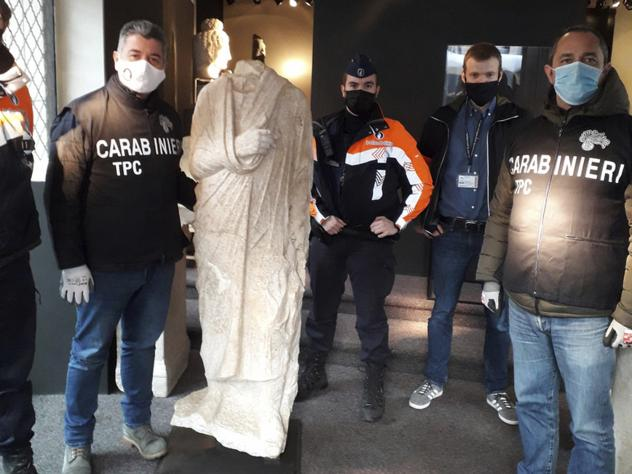 Carabinieri (Italian paramilitary police) officers of the art squad's archaeological unit pose with a headless Roman statue wearing a draped toga in Brussels on Wednesday, Feb. 3, 2021.