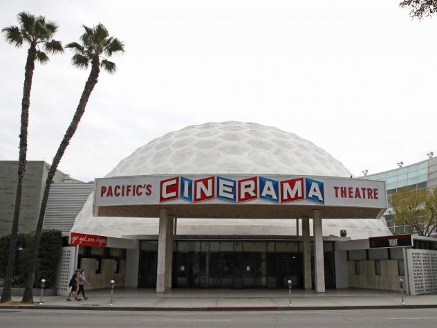 People wearing protective face masks walk by the closed Cinerama Dome theater during the coronavirus pandemic on April 18, 2020, in Los Angeles.