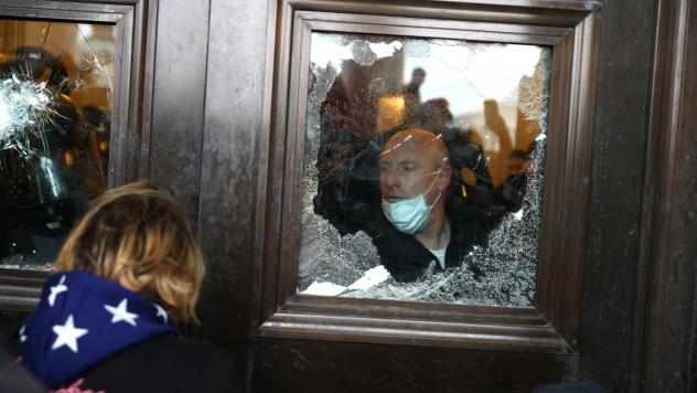 A Capitol police officer looks out of a broken window as pro-Trump rioters storm into the building on Jan. 6.