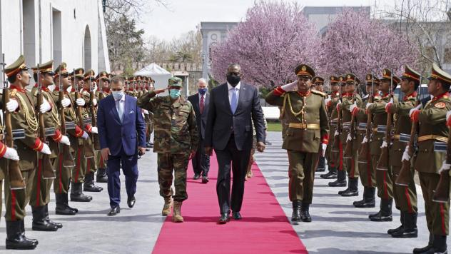 U.S. Defense Secretary Lloyd Austin, center, walks on the red carpet with Afghan officials as they review an honor guard at the presidential palace in Kabul, Afghanistan, on March 21. President Biden said the U.S. will withdraw all remaining troops from