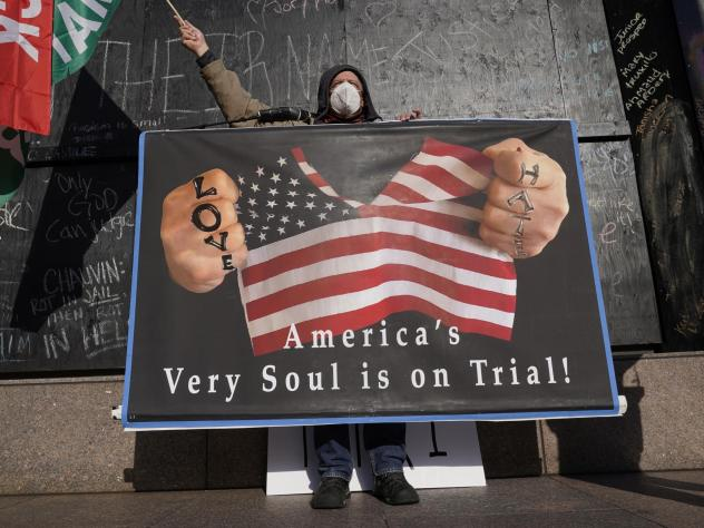 A protester stands across the street from the Hennepin County Government Center on Tuesday, where former Minneapolis police officer Derek Chauvin stands trial for the death of George Floyd.
