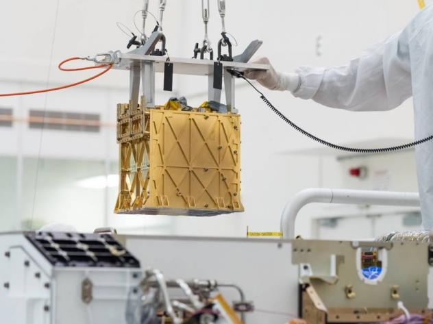 Technicians at NASA's Jet Propulsion Laboratory lower an instrument known as MOXIE, or the Mars Oxygen In-Situ Resource Utilization Experiment, into the belly of the Perseverance rover. NASA announced the instrument had produced oxygen from the Martian a