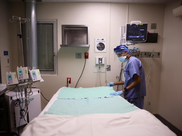 Intensive Care Unit nurse Subramanya Kirugulige prepares a bed for an arriving COVID-19 patient at Roseland Community Hospital in Chicago in December. A large study has found that people with severe initial cases of COVID-19 tend to be at greater risk of
