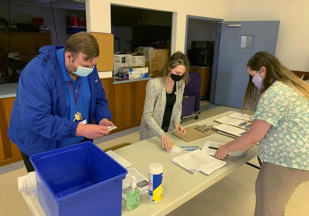 Holmes County, Ohio, General Health District staff members (from left) Michael Derr, Jennifer Talkington and Abbie Benton prepare materials for a COVID-19 vaccine clinic this month inside St. Peter's Catholic Church in Millersburg.