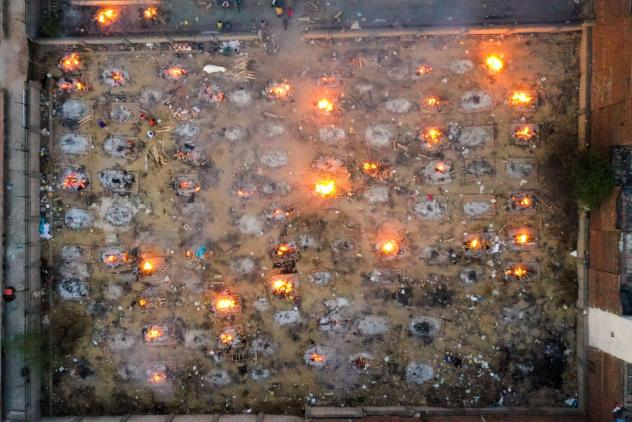 Victims of COVID-19 are cremated in funeral pyres this week in New Delhi. Scientists says the real death toll and number of infections are likely much higher than what the Indian government is reporting.